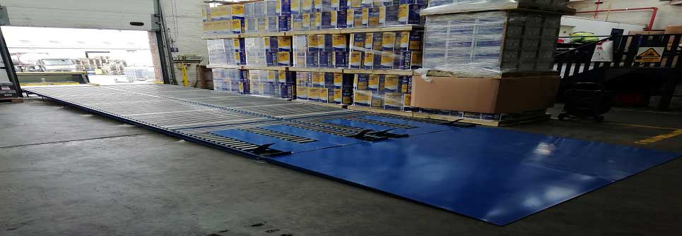 Pallet hold back and ramp conveyor